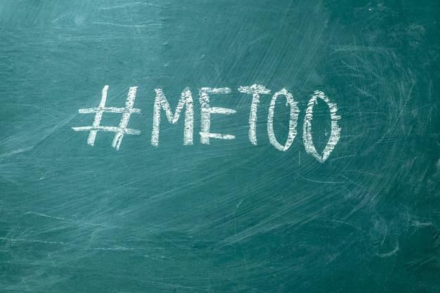 L'hashtag di metoo è scritto a mano con il gesso bianco su una lavagna verde.