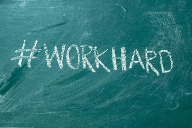 L'hashtag di workhard è scritto a mano con gesso bianco su una lavagna verde.