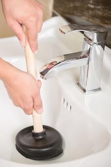 L'idraulico sta pulendo il lavandino con lo stantuffo.
