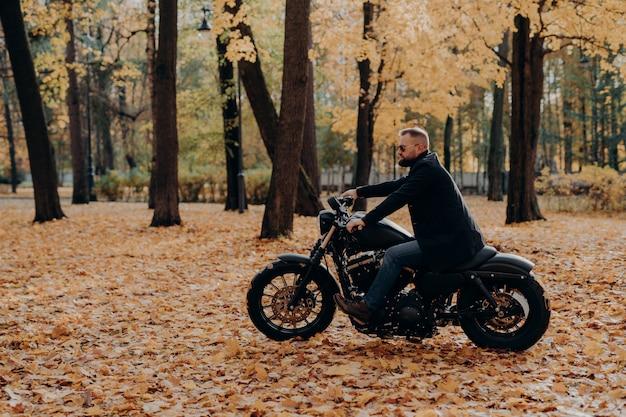 L'immagine all'aperto del motociclista maschio posa su una moto veloce, indossa sfumature, cappotto nero, gode di un giro nel parco in autunno