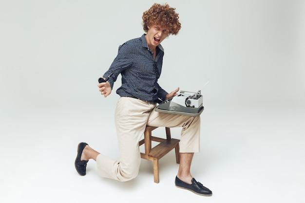 L'immagine del giovane uomo retro arrabbiato di grido si è vestita nella seduta e nella posa della camicia isolate. guardando la fotocamera con la macchina da scrivere tubo tenuta.