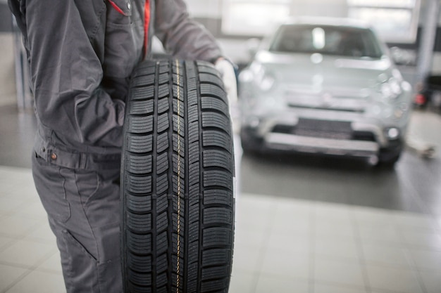 L'immagine dell'uomo nel supporto uniforme grigio e tiene la ruota di automobile con entrambe le mani. è pesante. l'auto bianca è dietro di lui.