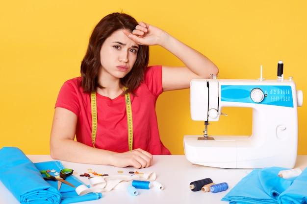 L'immagine della bella femmina del brunette si siede allo scrittorio funzionante con la macchina per cucire