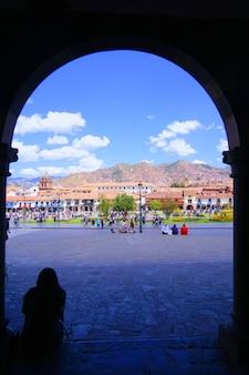 L'immagine della siluetta della donna che si siede alla porta dell'arco che osserva fuori la città di cusco, perù.