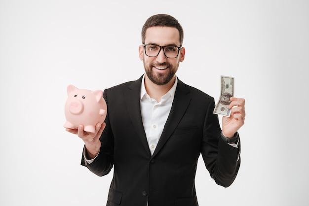 L'immagine di giovane uomo d'affari allegro sopra la parete bianca che mostra i pollici aumenta il gesto e la tenuta del salvadanaio.