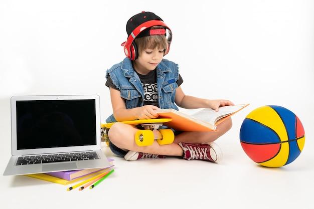 L'immagine di un ragazzo adolescente si siede sul pavimento in giacca di jeans e pantaloncini. scarpe da ginnastica con penny giallo, auricolari rossi, laptop e fare i compiti isolati