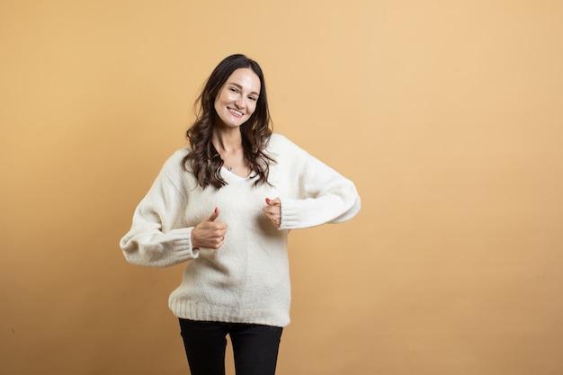 L'immagine di una giovane donna bellissima in un maglione bianco in posa su uno sfondo arancione isolato