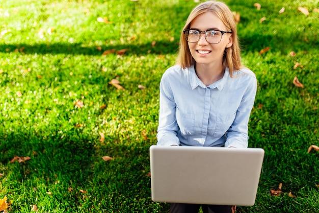 L'immagine di una giovane donna straordinaria, seduta in un parco, utilizzando un computer portatile, si siede su un prato verde.