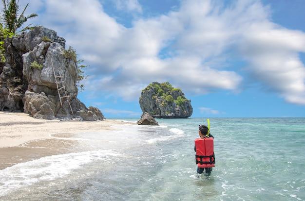 L'immagine dietro il ragazzo asiatico che indossa un giubbotto di salvataggio e le immersioni subacquee nel mare a koh lankajiu, chumphon, tailandia.