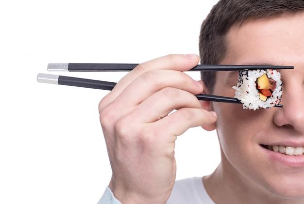 L'immagine divertente del giovane sta tenendo il pezzo di rotoli di sushi.