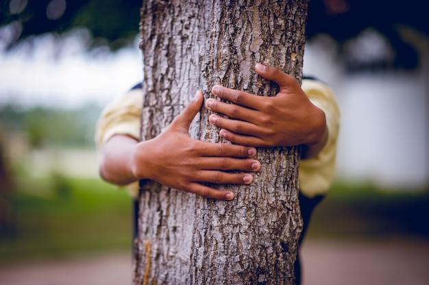 L'immagine ha abbracciato gli alberi di giovani uomini che amano la natura. concetto di cura naturale