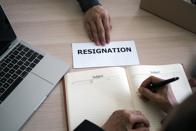 L'immagine in cima alla scrivania ha una mano d'affari per inviare una lettera di dimissioni alla direzione