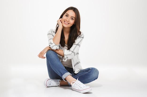 L'immagine orizzontale della donna castana con capelli castani che si siedono con le gambe ha attraversato sul pavimento e guardare sulla macchina fotografica con il sorriso, isolata sopra la parete bianca