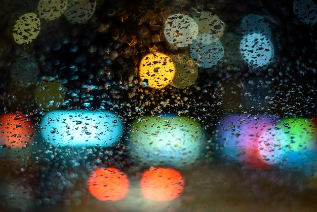 L'immagine piove sul finestrino della macchina, le luci della città di notte in un dio astratto sullo sfondo. profondità di campo, presa, soft focus