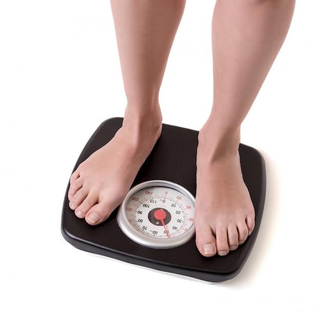 L'immagine potata dei piedi delle donne che stanno sulle bilance. concetto di dieta