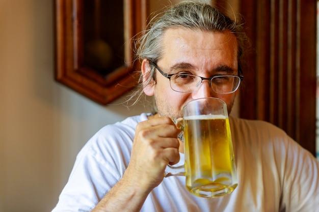 L'immagine ritagliata del bell'uomo sta bevendo birra