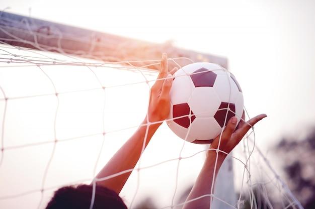 L'immagine ritagliata di giocatori sportivi che prendono la palla e il campo di calcio.