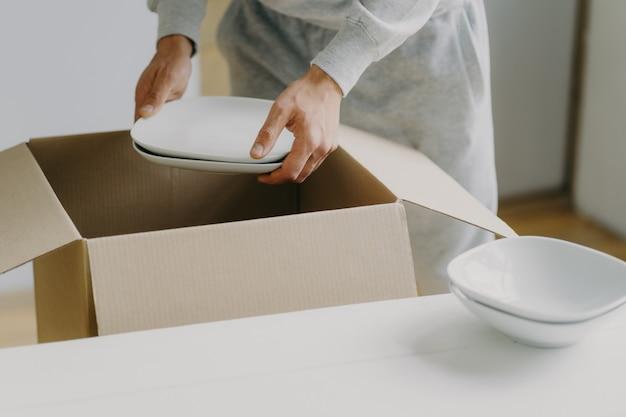 L'immagine ritagliata di un impegnato uomo senza volto sconosciuto disimballa scatole con piatti, tiene piatti bianchi, si trasferisce in un nuovo appartamento, riordina in cucina, ha una giornata commovente. tira fuori nuovi piatti. concetto di trasferimento
