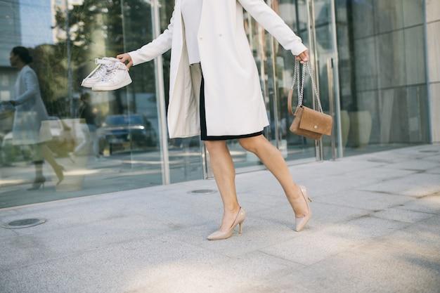 L'impiegato di ufficio femminile bello sta andando felicemente in palestra dopo una giornata lavorativa