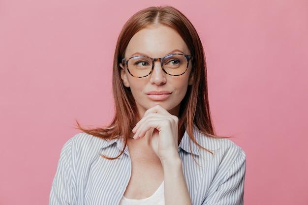 L'imprenditore attraente contemplativo indossa occhiali, camicia formale, tiene la mano sul mento