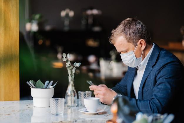 L'imprenditore maschio indossa una maschera medica durante l'epidemia di coronavirus, si siede al caffè