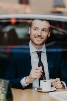 L'imprenditore maschio positivo in abiti formali, beve il caffè, ha un'espressione allegra, sembra felicemente a parte