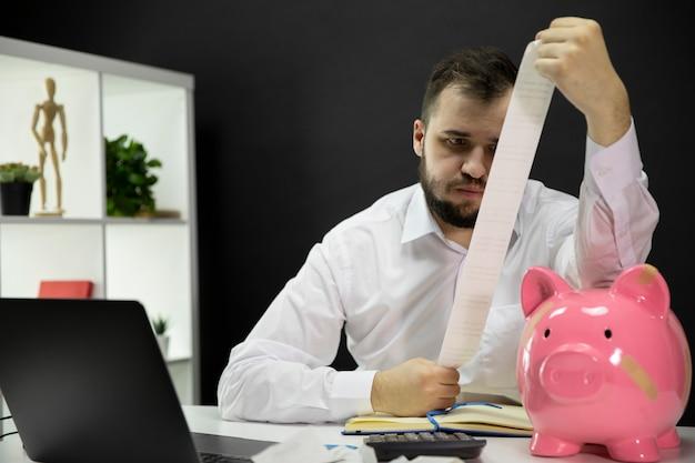 L'imprenditore stanco che guarda sugli assegni calcola le fatture finanziarie, porcellino salvadanaio rotto