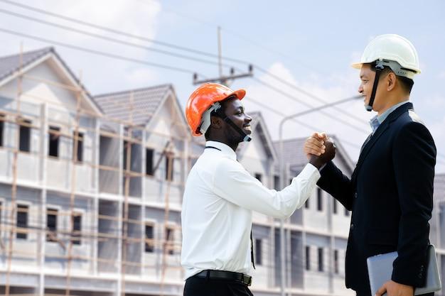 L'ingegnere architetto africano e asiatico si stringono la mano con l'edificio