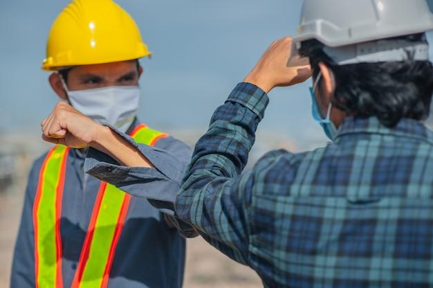 L'ingegnere asiatico della gente dell'uomo due stringe a mano la nuova costruzione normale del sito
