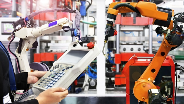 L'ingegnere controlla e controlla il braccio moderno dei robot di saldatura di automazione di alta qualità a industriale