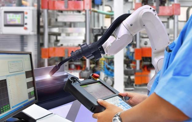 L'ingegnere controlla e controlla l'automazione moderna di alta qualità saldando il braccio bianco dei robot all'industria