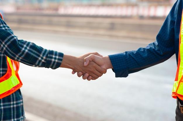L'ingegnere del lavoro di squadra stringe la mano accordo accordo successo di costruzione del progetto, il partner di supporto tecnico coopera la costruzione di edifici di lavoro dell'appaltatore di servizio di squadra.