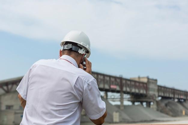 L'ingegnere minerario in camicia e casco bianchi supervisiona il lavoro del laboratorio di granito
