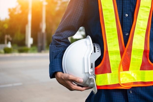 L'ingegneria tiene cappelli di sicurezza bianchi e palo elettrico