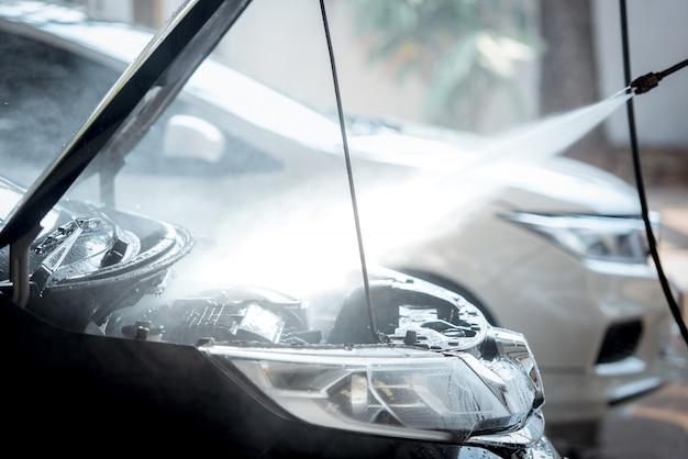 L'iniezione di lavaggio del motore durante il lavaggio dell'auto fa brillare e risplendere il motore del motore nero.