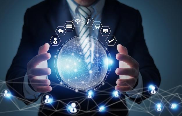 L'innovazione globale e il concetto di tecnologia di rete, uomo d'affari che tiene il pianeta sociale, la rete si collegano in tutto il mondo
