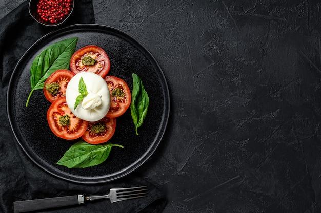 L'insalata dei pomodori e del burrata è servito sulla banda nera. sfondo scuro vista dall'alto. spazio per il testo