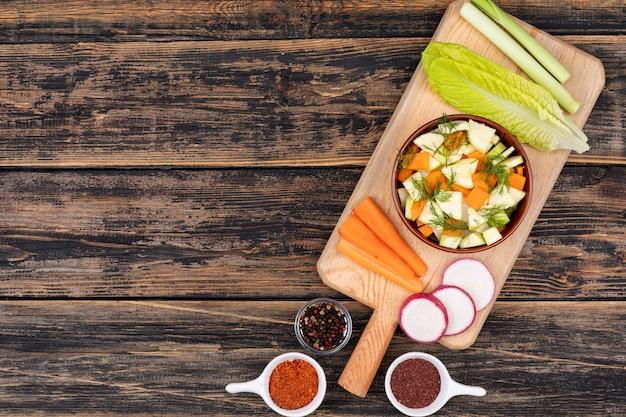L'insalata di carota in ciotola e verdure ceramiche è sulla vista superiore del tagliere di legno con lo spazio della copia