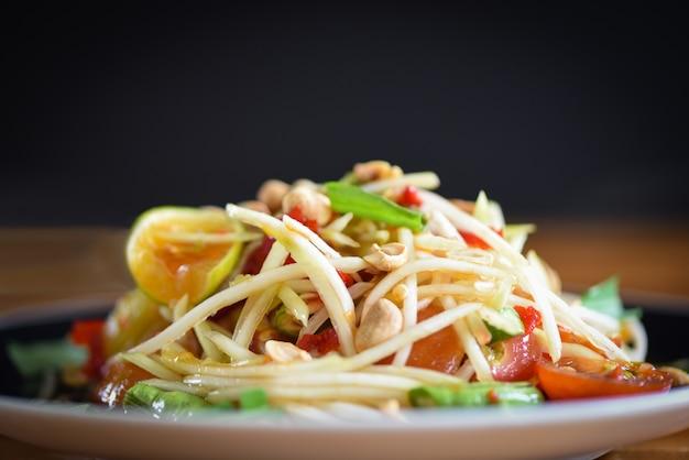 L'insalata di papaia è servita sul piatto con sfondo scuro