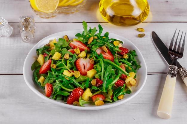 L'insalata fresca con la rucola, le fragole, l'ananas ed i pistacchi è servito sul piatto bianco sulla tavola di legno rustica