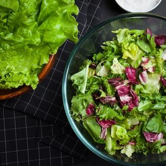 L'insalata vegetariana fresca si mescola in una ciotola di vetro trasparente.