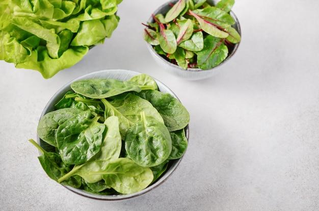 L'insalata verde fresca lascia in ciotole su una tavola concreta grigia.