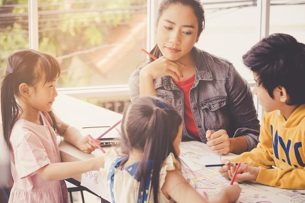 L'insegnante asiatico sta insegnando ai bambini nell'aula della scuola materna