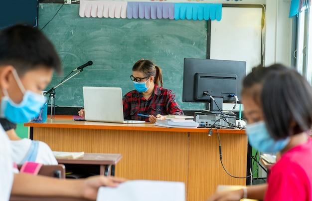 L'insegnante che indossa una maschera protettiva per proteggere dal covid-19 sta insegnando ai bambini delle scuole seduti in classe online, alla scuola elementare, all'apprendimento e al concetto di persone.