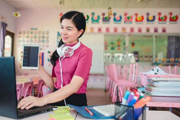 L'insegnante di asilo femminile asiatico sta insegnando agli studenti di asilo online. insegnanti e studenti utilizzano sistemi di videoconferenza online per insegnare agli studenti.