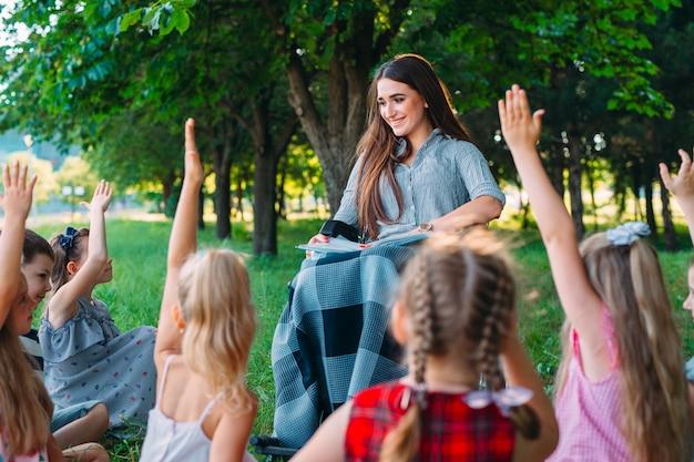 L'insegnante disabile tiene una lezione con i bambini nella natura. interazione di un insegnante in sedia a rotelle con gli studenti.