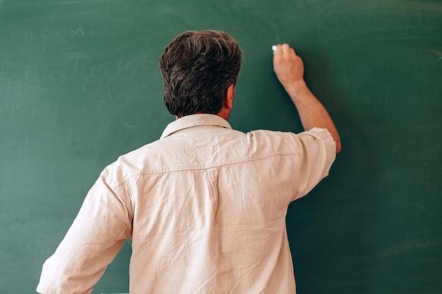 L'insegnante scrive alla lavagna e spiega una lezione.
