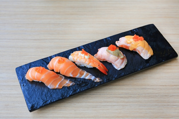 L'insieme dei frutti di mare dei sushi è servito sul piatto di pietra nero sulla tavola di legno. cucina giapponese.