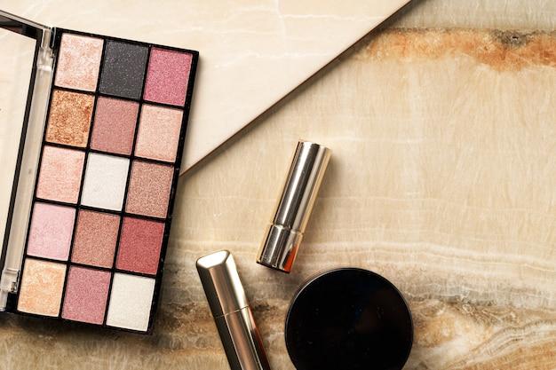 L'insieme della donna compone i cosmetici su fondo di pietra.