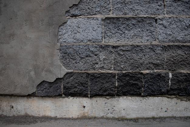 L'intonaco si è sbriciolato dal muro a causa del tempo e dell'umidità. mattoni di cemento espanso scoperto.